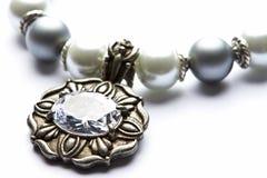 Costume Juwelery. Silver designer costume jewelery in macro on white background Royalty Free Stock Photography