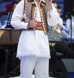 Costume national roumain sur le chanteur exécutant sur l'étape photos stock