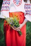 Costume national russe Mains femelles avec le bouquet du wildflowe images libres de droits