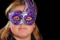Costume Party. Closeup of a young blonde girl wearing a venetian mask, shot against a black background Royalty Free Stock Images