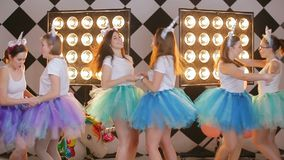 Costume party holiday concept - cheerful unicorn girl`s dancing battle. Group party studio girl`s dancing fun and look straight into the camera on girl s night stock video footage