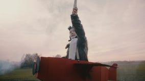 Costume plat de port de carton d'amusement de petite fille d'aviateur tenant la fumée bleue de couleur jouant un pilote sur le mo banque de vidéos