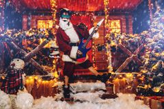 Costume of rocker santa. Cool rocker in Santa Claus cose and luminous glasses plays the guitar near a festively decorated house royalty free stock photo