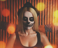 Costume Skeleton Woman with Party Lights. A woman is wearing skeleton makeup on her face with orange party lights for a halloween celebration or costume idea stock images