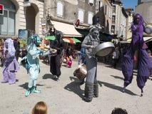 Costumed artyści bawić się muzykę na stilts Zdjęcia Royalty Free