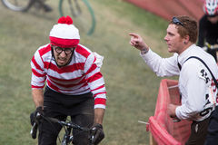 Costumed Bicycle Racer - Where's Waldo?. A Costumed Bicycle Racer dressed as Where's Waldo gets heckled by a bystander at a Halloween-themed cyclocross bicycle Royalty Free Stock Images