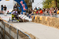 Costumed Competitor Falls Hard From Vehicle In Soap Box Derby Stock Image