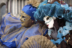 Costumed couple at Venice Carnival 2011. VENICE - MARCH 1, 2011: An unidentified couple in bright costumes during Venice Carnival 2011, S. Marco square, Venice Stock Images