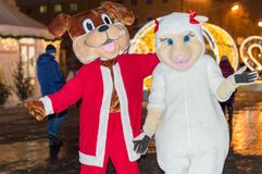Costumed heroes of the white sheep and a large dog near the New Year tree, are photographed with visitors. royalty free stock photography