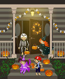 Costumed kids dressed up for trIck or treat. Costumed kids dressed up for trick or treat, stand at the stairs. Halloween decorated front door and porch with Royalty Free Stock Images