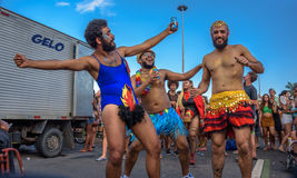 Costumed man in a leotard with hair and fire between his legs with two his friends in mini skirts in Flamengo Park, Carnaval 2017 Stock Images