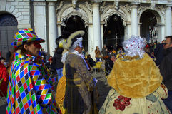 Costumed people at Venice Carnival. Disguised people and  people relaxing in outdoor cafe  on Venice square,Italy.Photo taken on February 8th,2015 Stock Photography