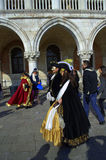 Costumed people at Venice Carnival. Doges Palace arcades and disguised people and  tourists sightseeing on Venice square,Italy.Photo taken on February 8th,2015 Royalty Free Stock Photos