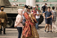 Costumed people walk on the Palace Square Royalty Free Stock Images