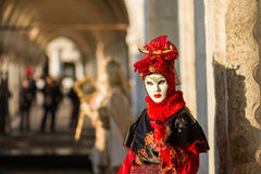 Costumed person in Venetian mask. During Venice Carnival in Venice Royalty Free Stock Photo