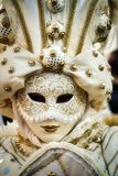 Costumed Reveler of the Carnival of Venice. A costumed reveler of the Carnival of Venice in a white and gold costume looking directly at the camera Stock Photos