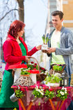 Costumer buying flower in flower shop. Female florist selling men plant in front of flower shop royalty free stock image