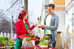 Costumer buying flower in flower shop. Female florist selling men plant in front of flower shop stock photos
