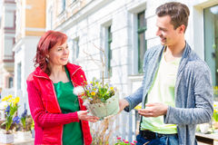 Costumer buying flower in flower shop. Female florist selling men plant in front of flower shop stock image
