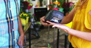 Costumer making payment through credit card. In flower shop stock video