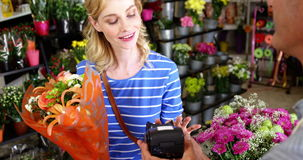 Costumer making payment through credit card in flower shop. Slow motion of costumer making payment through credit card in flower shop stock video