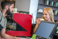 Costumers in a coffee shop. Two beautiful young women buying coffee in a coffee shop from a barista guy stock photos