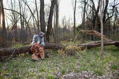 Costumes animaux de port de couples se reposant par l'arbre Photo stock