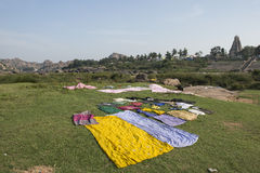 Costumes and traditional cloths lying in a field, Hampi, India. Costumes and traditional cloths lying in a field, in the archaeological complex of temples and stock photos