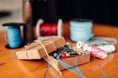 Costura, caja con las gotas en la tabla de madera Foto de archivo