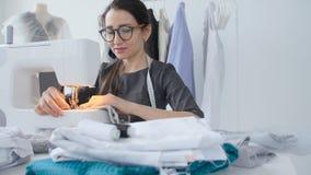 Costura de la afición y un concepto de la pequeña empresa La costurera bonita joven de la mujer cose en la máquina de coser Sastr almacen de metraje de vídeo