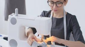 Costura de la afición y un concepto de la pequeña empresa La costurera bonita joven de la mujer cose en la máquina de coser Sastr almacen de video