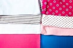 Costura de la tela Mono azul y rosado doblado en fondo rosado y azul minimalistic pañal para el muchacho y la muchacha recién nac Imagen de archivo libre de regalías
