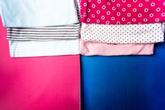 Costura de la tela Mono azul y rosado doblado en fondo rosado y azul minimalistic pañal para el muchacho y la muchacha recién nac Foto de archivo libre de regalías