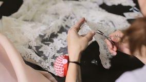 Costura de los vestidos de boda Visión superior La costurera cortó el cordón para los vestidos de boda almacen de metraje de vídeo