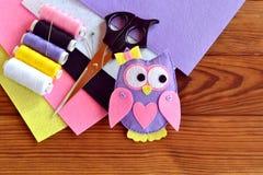 Costura de un juguete del búho del fieltro Búho púrpura adornado con el arco, los botones y el corazón Imagenes de archivo