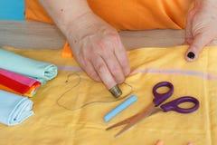 Costura y mano que acolchan en el taller de una mujer del sastre - en la mesa del hilo, tijeras Imágenes de archivo libres de regalías