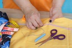 Costura y mano que acolchan en el taller de una mujer del sastre - en la mesa del hilo, tijeras Imagen de archivo