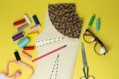 Costurando acessórios e tela em um fundo do yelow Linhas de costura, pinos, teste padrão e centímetro costurar Para costurar em c fotografia de stock royalty free
