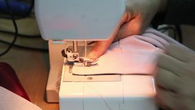 Costurando as mãos idosas do ` s da mulher do processo atrás da máquina de costura filme