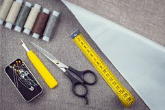 Costurando a composição do teste padrão com tesouras, carretéis da linha, pinos, fita de medição imagem de stock royalty free