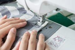 Costurando o processo, a máquina de costura costura as mãos das mulheres que costuram o Mac Foto de Stock Royalty Free