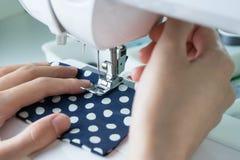 Costurando o processo, a máquina de costura costura as mãos das mulheres que costuram o Mac Fotos de Stock