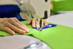 Costurando o processo - mãos do ` s das mulheres atrás de sua costura Fotos de Stock