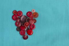 Costurando os botões encontram-se na forma de um coração em um fundo monofônico de turquesa O conceito do amor, bordado, sentimen imagem de stock