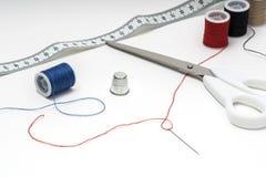 Costure ferramentas na tabela branca com os skeins múltiplos em ambos os lados Fotografia de Stock