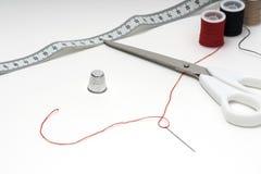 Costure ferramentas na tabela branca com skeins múltiplos Imagem de Stock