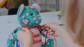 Costure a mulher, toymaker que amarra a curva no pescoço do urso de peluche video estoque