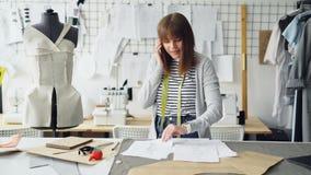 A costureira atrativa nova está discutindo projetos da roupa no telefone celular e está verificando esboços ao trabalhar nela filme