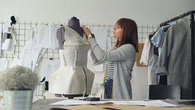 A costureira atrativa nova está medindo o manequim do ` s do alfaiate com fita para fazer o vestuário novo com estas medidas Dia  filme