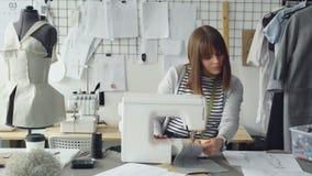 A costureira atrativa nova está trabalhando na máquina de costura e está olhando esboços do vestuário do ` s das mulheres em seu  filme